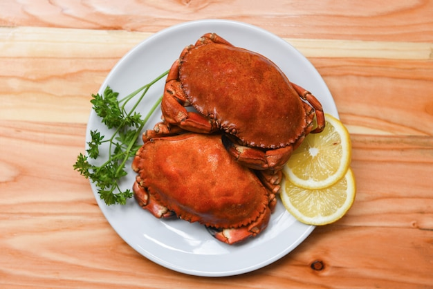 Crabe cuit sur une assiette blanche avec des herbes au citron et des épices salade de fruits de mer bouillie aux crabes rouges