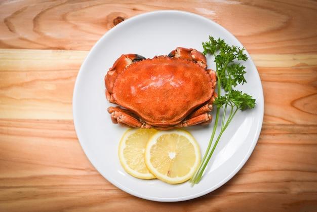 Crabe cuit sur une assiette blanche avec des herbes et des épices au citron