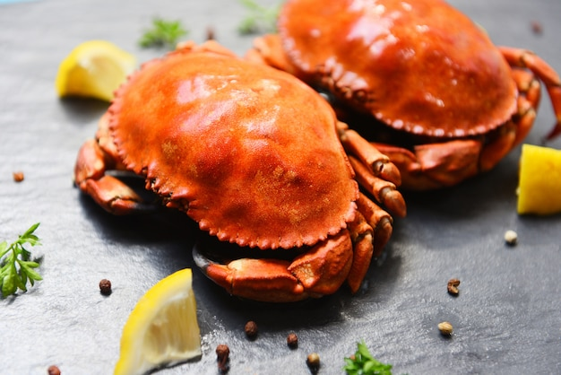 Crabe cuit sur une assiette noire avec des herbes et des épices au citron
