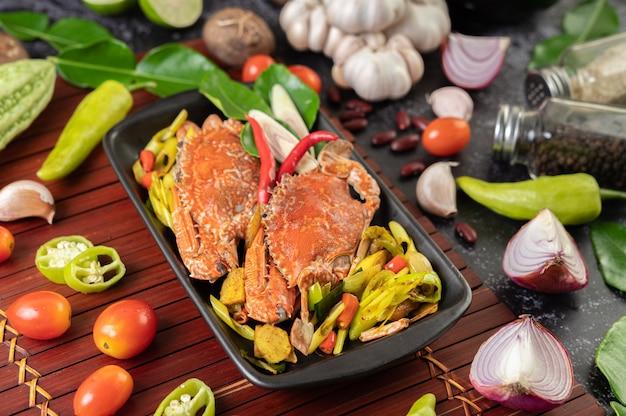 Crabe frit au curry en poudre dans une assiette avec poivrons et tomates.