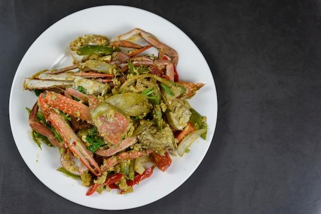 Crabe sauté à la poudre de cari sur une assiette blanche, isolé sur fond noir, cuisine thaïlandaise (bu pad pong karee)
