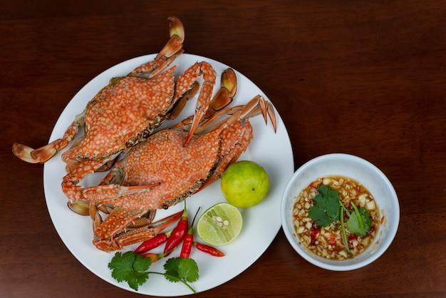 Crabes bleus avec trempette dans une assiette, sur un fond en bois, vue de dessus