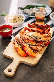 Crabes de boue géants cuits à la vapeur, crabes de fleurs cuites à la vapeur et crevettes grillées (crevettes) sur une planche à découper en bois.