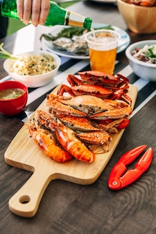 Crabes de boue géants cuits à la vapeur, crabes de fleurs cuits à la vapeur et crevettes grillées (crevettes) dans une planche à découper en bois avec de la bière à la main.