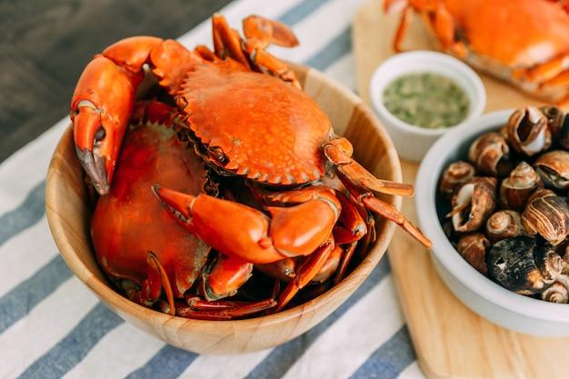 Crabes de boue géants cuits à la vapeur dans un bol en bois, servis avec une sauce thaïlandaise épicée aux fruits de mer.