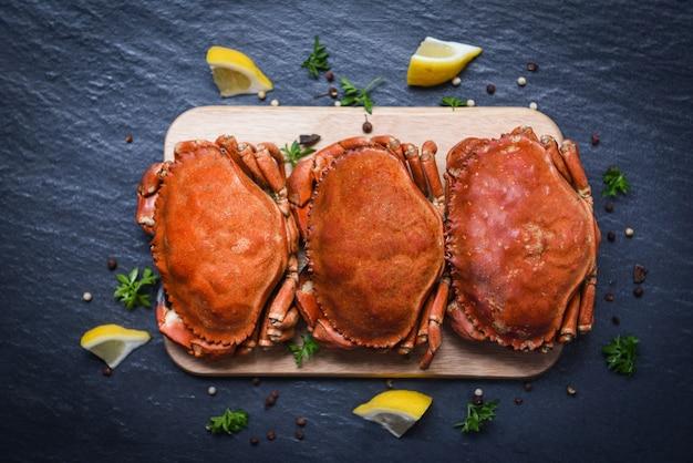 Crabes cuits sur une planche en bois au citron sur plaque servis sur plaque sombre