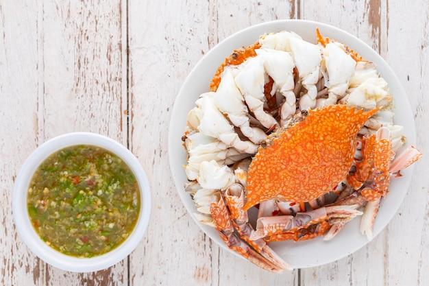 Crabes cuits à la vapeur avec trempette épicée dans une assiette en céramique blanche sur fond de texture de bois ancien blanc avec espace de copie pour le texte, vue de dessus, crabe de natation bleu, crabe de fleur, crabe bleu