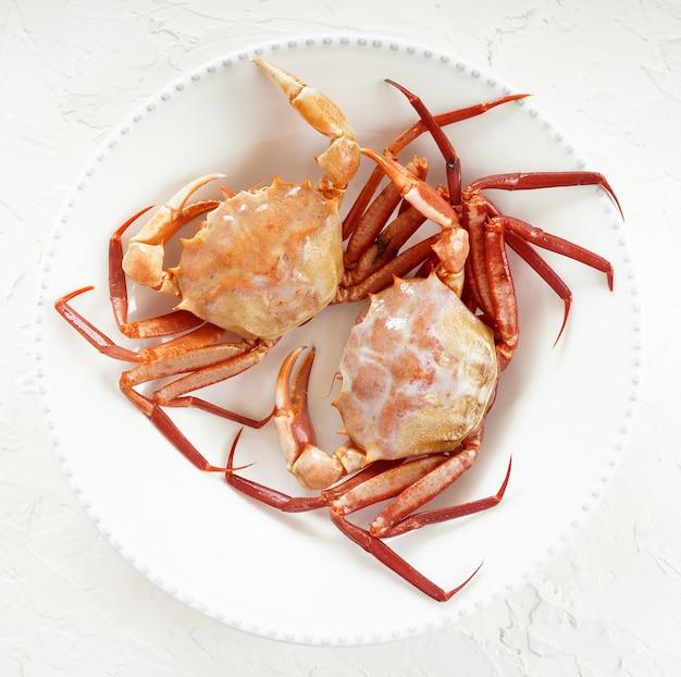 Crabes frais crus sur la plaque blanche