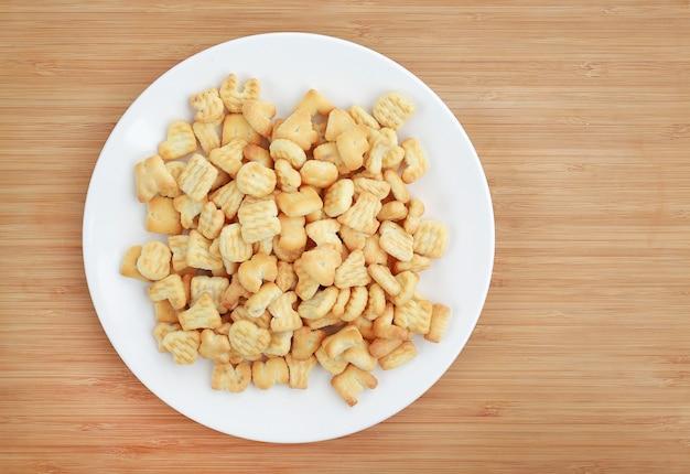 Cracker ou cookie alphabet lettre abc en plaque blanche sur fond en bois avec espace de copie.