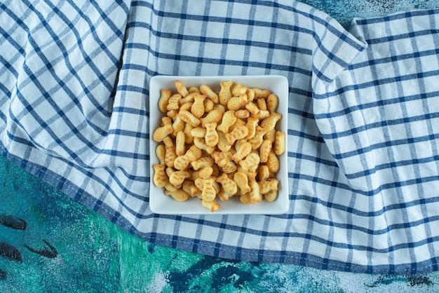 Cracker fish dans un bol sur un torchon, sur la table bleue.