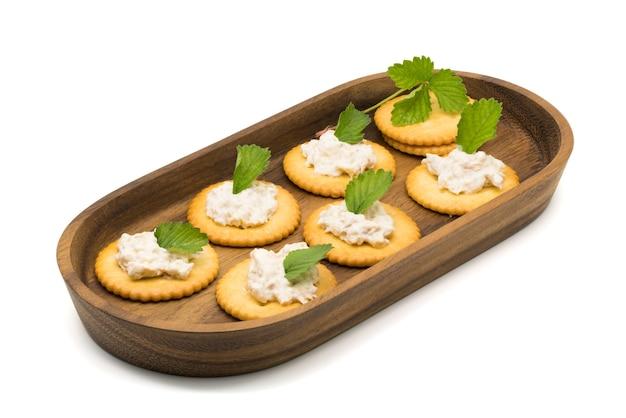 Cracker avec salade de thon dans un plateau en bois sur fond blanc
