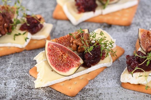 Cracker avec une tranche de camembert, de confiture, de figues et de noix. une excellente idée de collation pour des vacances, un pique-nique ou une fête.