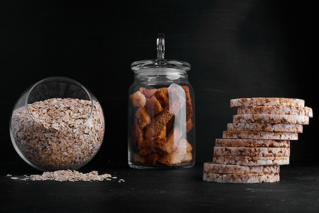 Crackers, une tasse de céréales et de fruits secs sur fond noir.