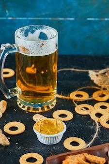 Crackers et un verre de bière sur une surface sombre.