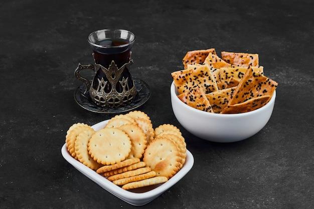 Crackers avec un verre de thé sur fond noir