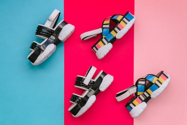 Cracovie, pologne - 25 avril 2019: ensemble de chaussures féminines à la mode. sandales pour femmes multicolores à la mode de l'été sur un coin haut sur fond bleu et rose. chaussures vogues et élégantes pour les filles modernes.