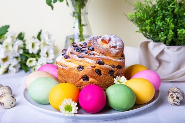 Craffin (cruffin) aux raisins secs et fruits confits. pain de pâques kulich et oeufs peints. fête de pâques. fermer.