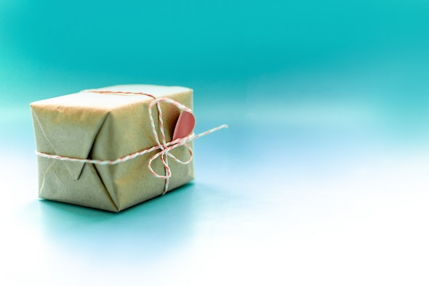 Craft papier enveloppé présente boîte artisanale ruban noeud papillon sur fond bleu, vue de dessus