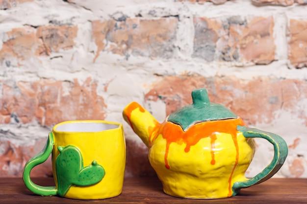 Craft théière en céramique à la main et tasse pour la cérémonie du thé debout sur une vieille étagère en bois contre le mur de briques.