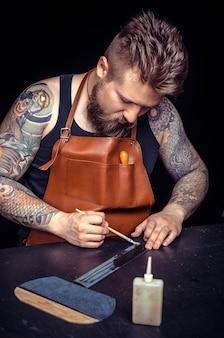 Craftsman effectue le travail du cuir pour un nouveau produit dans son atelier de tannerie.