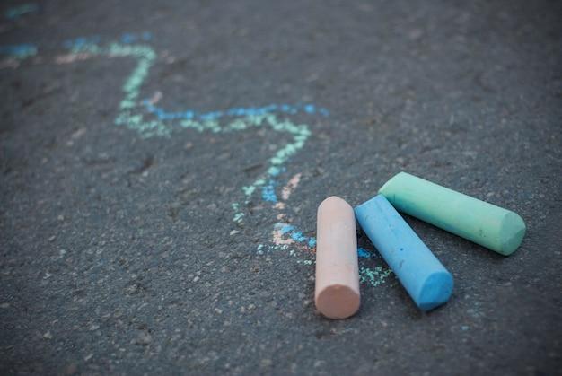 Craie sur l'asphalte texturé. lignes de dessin colorées. enfance et parentalité. éducation.