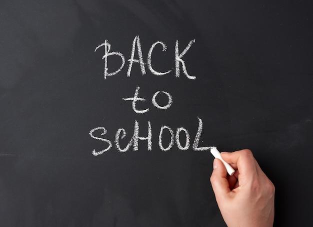 Craie blanche retour à l'école sur tableau noir, main tient un morceau de craie blanche