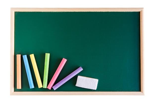 Craie de couleur et gomme de tableau blanc sur tableau blanc vert isolé sur blanc. avec flic