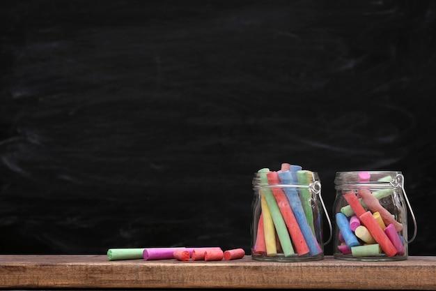 Craie multicolore dans un bocal sur fond de tableau noir