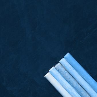 Craies bleues classiques sur tableau noir closeup