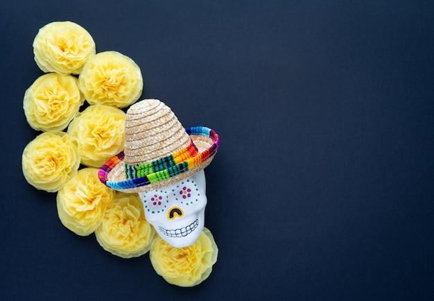 Crâne avec chapeau mexicain et fleurs de papier jaune cempasuchil sur fond noir