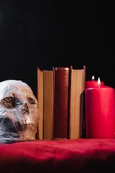 Crâne dans un sac en plastique avec des livres et des bougies