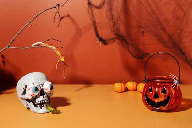 Crâne drôle de paysage d'halloween avec des yeux de bonbons et une prise de lampe de poche de chandelier de ver de gelée