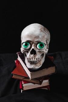 Crâne effrayant avec des yeux de jouet drôle sur une pile de livres