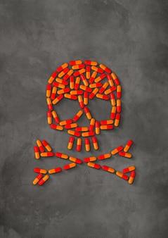 Crâne fait de pilules capsule orange isolé sur fond de béton foncé. illustration 3d