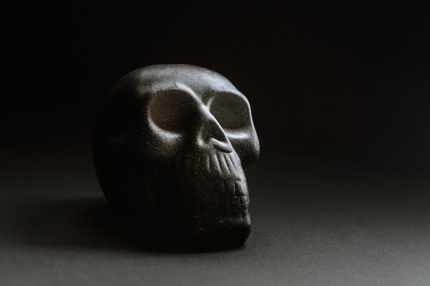 Un crâne sur un fond sombre, couché sur une surface plane
