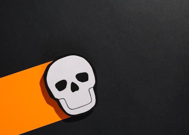 Crâne d'halloween fait main sur une bande de papier orange
