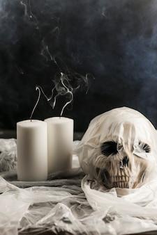 Crâne humain dans un sac en plastique avec des bougies blanches