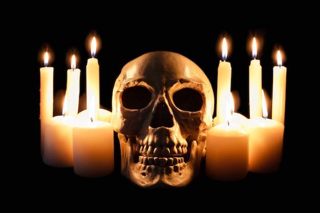 Crâne humain parmi des bougies allumées dans l'obscurité, nature morte effrayante, autel.
