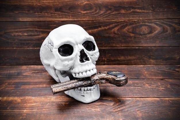 Crâne humain avec un pistolet sculpté vintage dans sa bouche sur une surface de planche de bois.