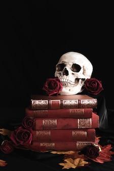 Crâne humain avec des roses sur les livres