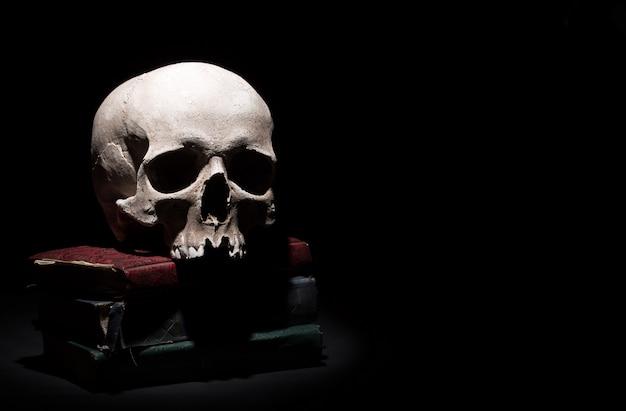 Crâne humain sur de vieux livres sur fond noir sous faisceau de lumière