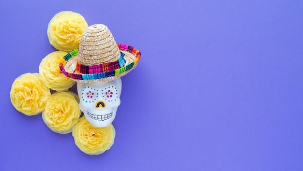 Crâne mexicain avec chapeau à fleurs jaunes de papier cempasuchil sur violet
