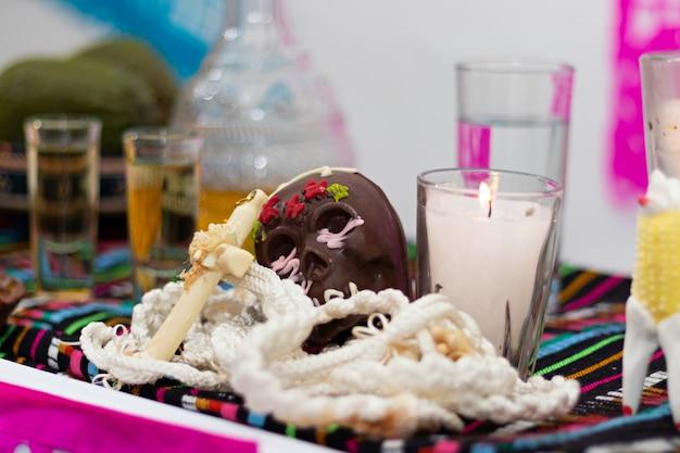 Un crâne mexicain typique du jour des morts en chocolat avec un chapelet et une bougie dans une offrande typiquement mexicaine du jour des morts dans une maison mexicaine