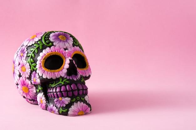 Crâne mexicain typique avec des fleurs peintes en rose.
