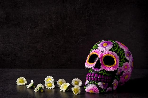 Crâne mexicain typique peint et fleurs sur fond noir