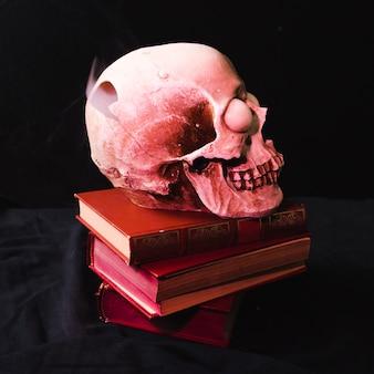 Crâne avec la nuque fumée sur les livres