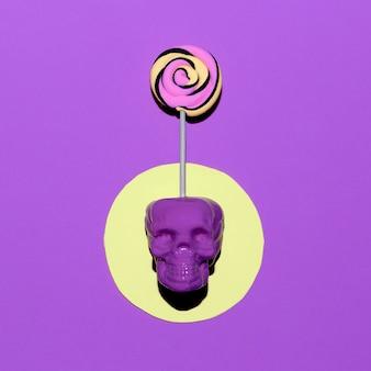 Crâne et sucette. mode d'humeur pourpre de bonbons. art plat