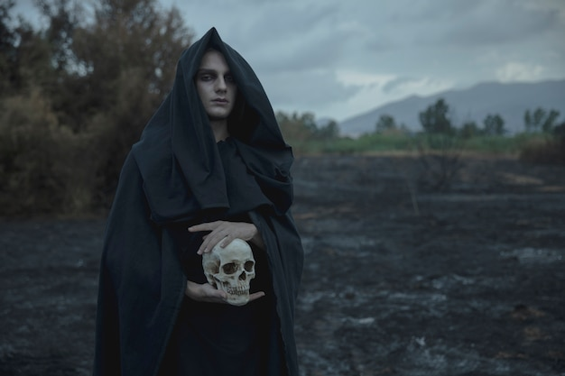 Crâne tenu par un mage en vêtements noirs