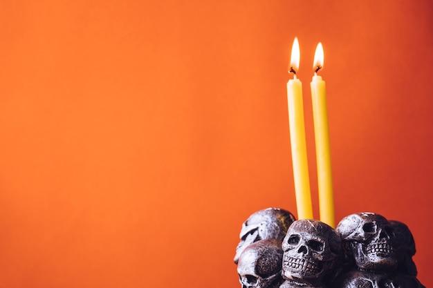 Crânes avec une bougie allumée sur un fond de couleur orange. espace libre pour le texte