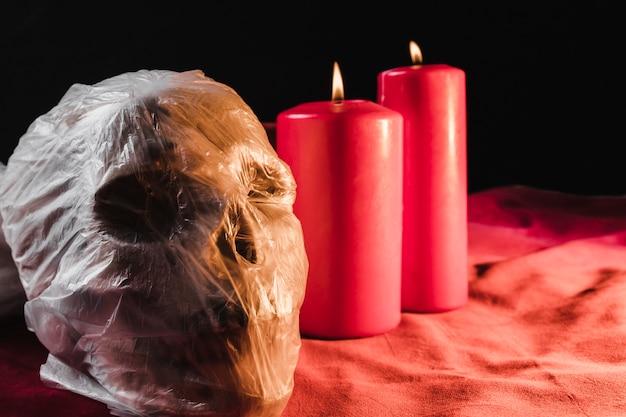 Cranium emballé dans un sac en plastique et des bougies allumées
